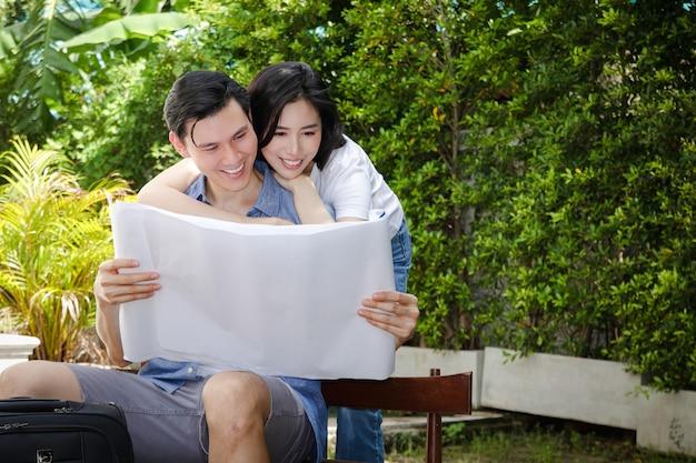Asiatische männer- und frauenpaare halten sie die blaupause, das neue haus ist glücklich, eine familie zusammen zu bauen.