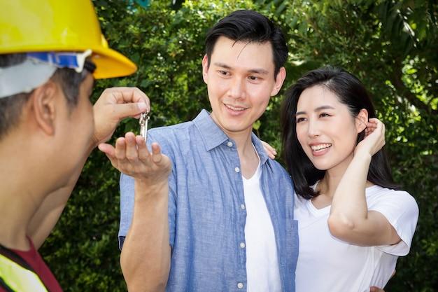 Asiatische männer- und frauenpaare holen sie sich die hausschlüssel vom hausinspektionsingenieur. beide waren glücklich mit ihrem neuen zuhause. das konzept der familiengründung.