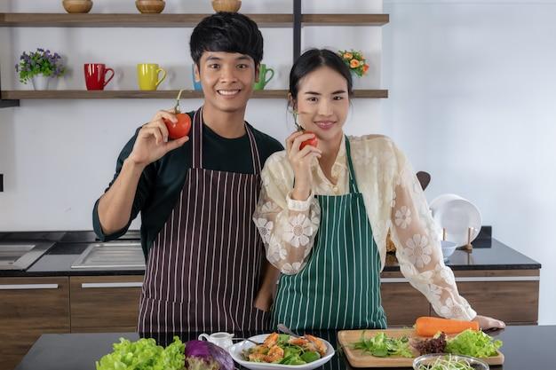 Asiatische männer und junge frauen zeigen tomaten