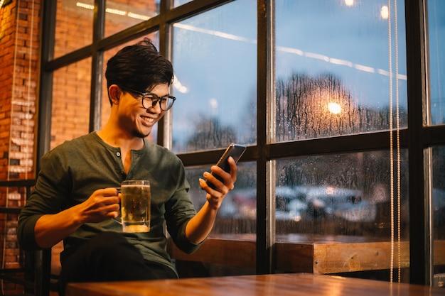 Asiatische männer unterhalten sich auf ihren mobiltelefonen und trinken bier, um sich nach dem arbeiten glücklich zu entspannen.