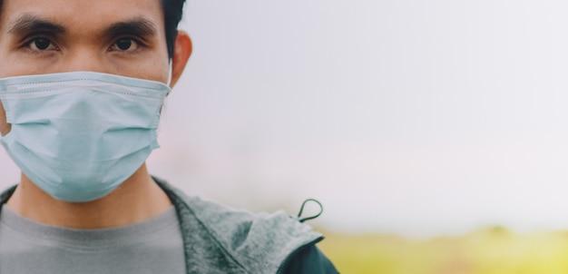 Asiatische männer verwenden eine chirurgische maske oder eine gesichtsmaske, um das coronavirus 2019 oder covid 19 in der öffentlichkeit zu schützen