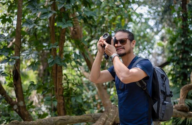 Asiatische männerrucksäcke und reisende, die zusammen und glücklich gehen, machen foto auf wald, entspannen sie zeit auf urlaubskonzeptreise