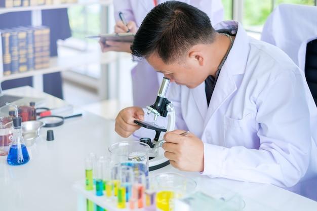 Asiatische männliche doktoren oder wissenschaftler, die mikroskop verwenden, um über die biologie am wissenschafts-labor zu erforschen