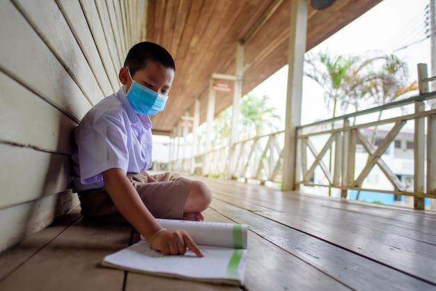 Asiatische männliche grundschüler mit medizinischer maske zur vorbeugung des coronavirus