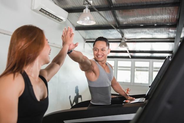 Asiatische männliche high five beim training auf dem laufband