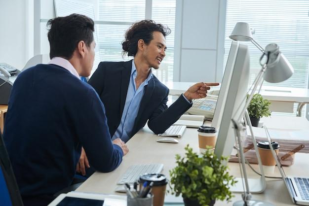 Asiatische männliche kollegen, die zusammen bildschirm im büro betrachten