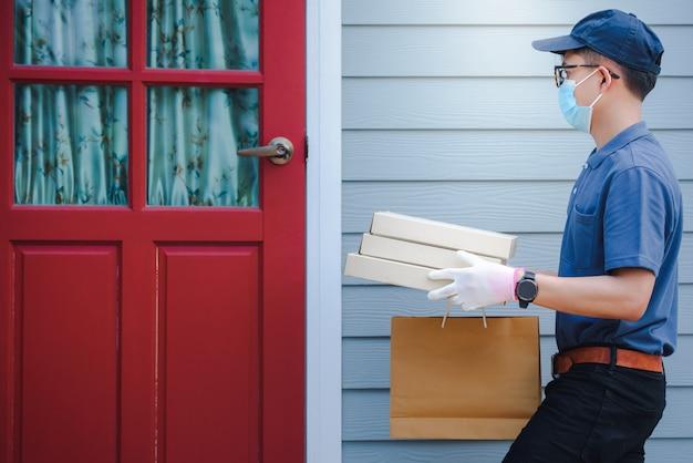 Asiatische männliche zusteller tragen schutzmasken und medizinische handschuhe für die online-zustellung. hauslieferdienst unter quarantänebedingungen des ausbruchs des coronary disease-19-virus