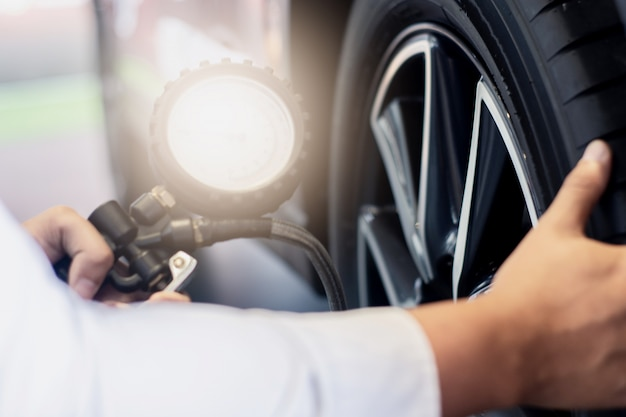 Asiatische mannautoinspektion maßmenge aufgeblasenes gummireifenauto schließen sie herauf handholdingmaschine aufgeblähtes manometer für autoreifendruckmessung für automobil, automobilbild