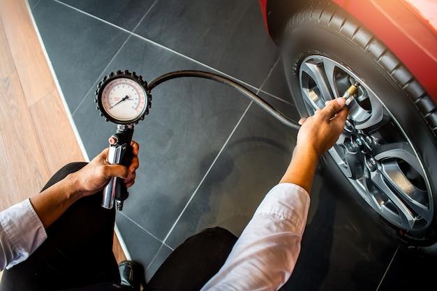 Asiatische mannautoinspektion messen sie die menge aufgeblasener gummireifen