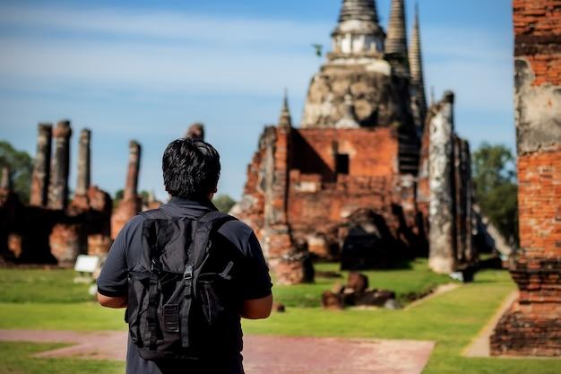 Asiatische mannreisende, die karte einem tempel phar sri sanphet ayutthaya betrachten.