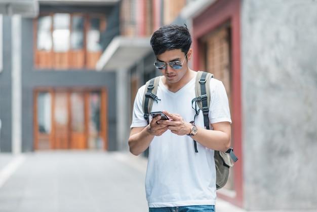 Asiatische mannrichtung des reisenden auf standortkarte in peking, china