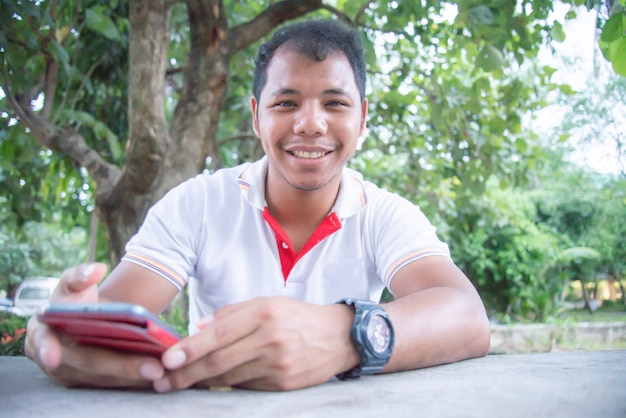 Asiatische mannsonnenbräunehaut mit lächeln unter verwendung und note am handy. er sieht glücklich aus. konzept von den leuten, die tragbare geräte bearbeiten. social media-süchtigkonzept. online einkaufen. tiefenschärfe. glücklich.