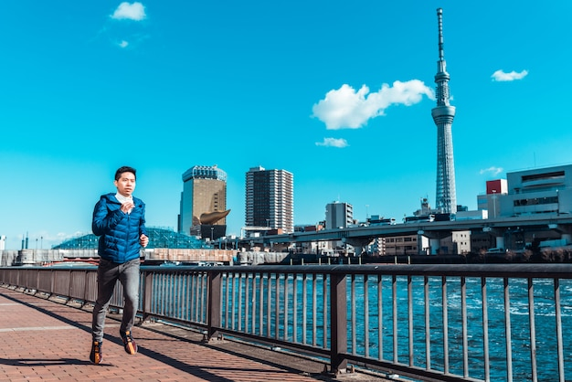 Asiatische mannübung, die durch fluss in tokyo, japan läuft