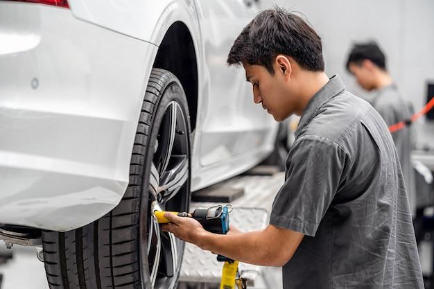 Asiatische mechaniker, welche die autoräder in der wartungswerkstatt auf im ausstellungsraum überprüfen, der ein teil der berufsarbeit des ausstellungsraums, des technikers oder des ingenieurs für kunden, autoreparaturkonzept ist