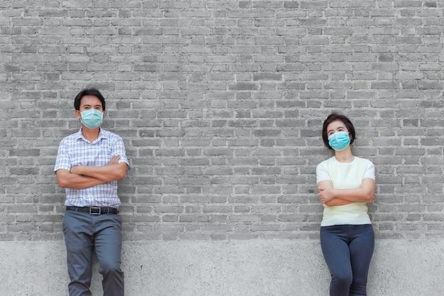 Asiatische menschen mittleren alters, die eine maske tragen und sich sozial distanzieren, um die verbreitung von covid-19 zu vermeiden