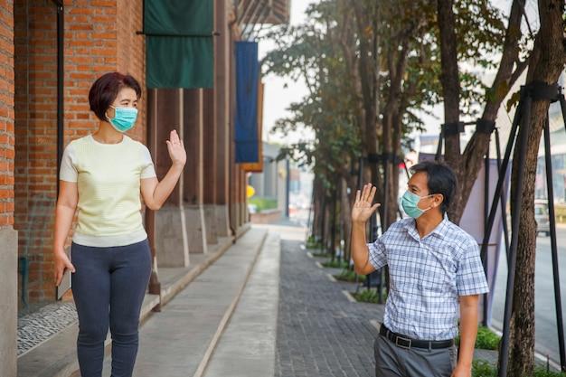 Asiatische menschen mittleren alters tragen eine maske und halten soziale distanz, um die verbreitung von covid-19 zu vermeiden