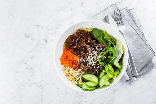Asiatische mittagspause mit rindfleisch. nudeln, grüne blätter und gemüse auf marmortisch mischen. draufsicht, kopierraum