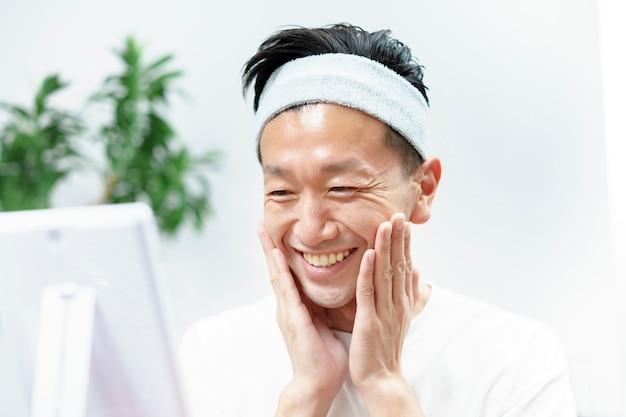 Asiatische mittlere männer, die hautpflege im raum tun