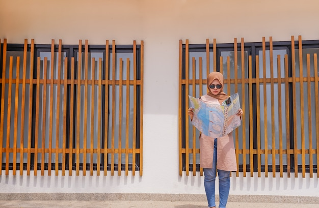 Asiatische moslemische frau des reisenden schauen und halten in der handkarte, leute, die reise planen
