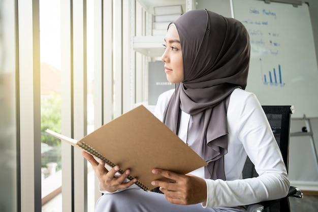Asiatische moslemische frau, die ein buch im büro liest. lebensstil der modernen moslemischen leute, das porträt des moslems.