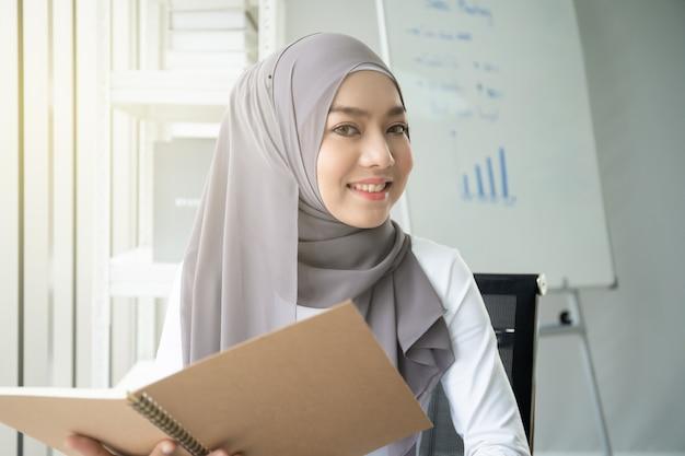 Asiatische moslemische frau, die ein buch im büro liest. lebensstilkonzept der modernen moslemischen leute, das porträt des moslems.