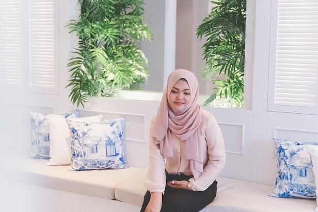 Asiatische moslemische frau, die einen guten tag sitzt auf der weißen tabelle im schönen hellen leben mit grünpflanzen hat
