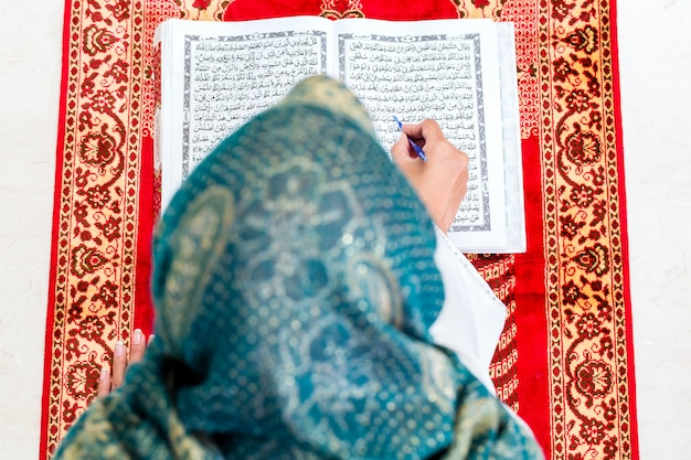 Asiatische moslemische frau, die koran oder quran studiert