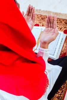 Asiatische moslemische frau, die mit dem koran betet