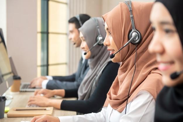 Asiatische moslemische frauen, die im kundenkontaktcenter mit team arbeiten