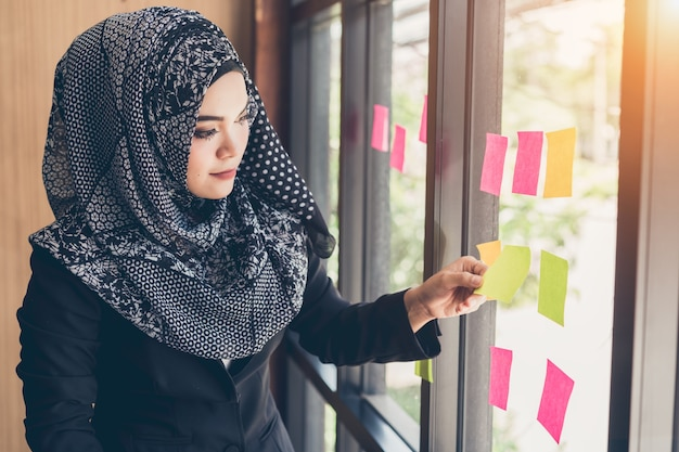 Asiatische moslemische geschäftsfrau-hand, die klebrige anmerkungen auf glaswand auswählt.