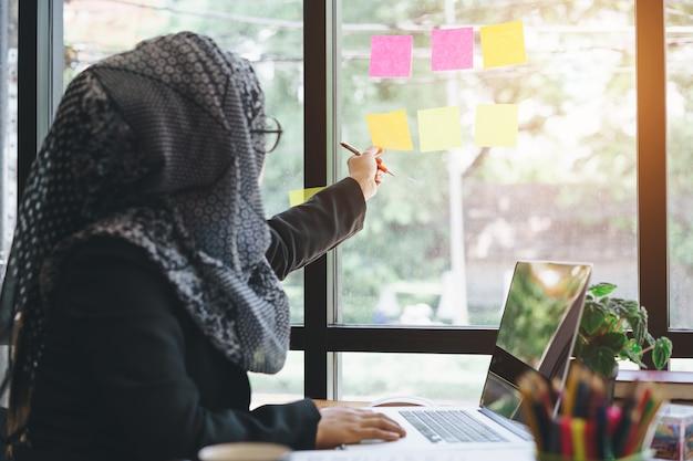 Asiatische moslemische geschäftsfrau, welche die hand auswählt klebrige anmerkungen über glaswand erreicht.