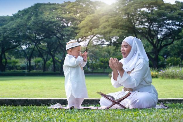 Asiatische moslemische mutter, die seinen kleinen sohn unterrichtet, zum gott mit rosenbeet am park zu beten