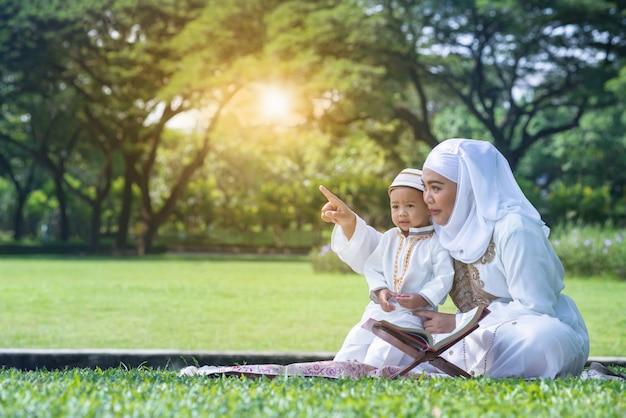 Asiatische moslemische mutter und ihr sohn, die qualitätszeit am park, an der moslemischen mutter und am sohnkonzept genießt
