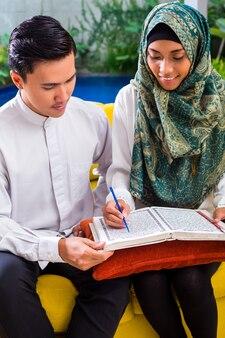 Asiatische moslemische paare, die zusammen koran oder quran lesen