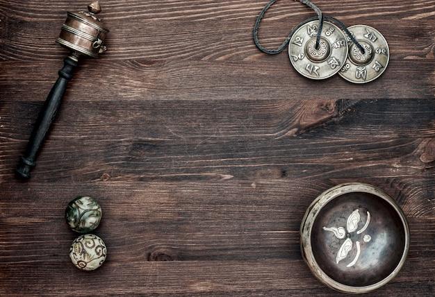 Asiatische musikalische religiöse gegenstände für meditation und alternativmedizin auf einer braunen holzoberfläche
