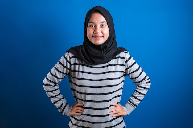 Asiatische muslimische college-studentin mit hijab, die freundlich mit verschränkten armen lächelt