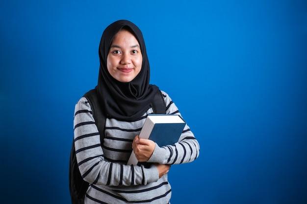 Asiatische muslimische college-studentin mit hijab lächelnd freundlich mit großem buch