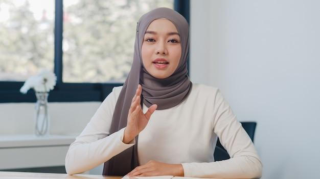Asiatische muslimische dame, die sich die kamera anschaut, spricht mit kollegen über den plan im videoanruf in einem neuen normalen büro.