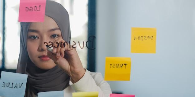 Asiatische muslimische dame schreibt informationen, strategie, erinnerung auf glastafel im neuen normalen büro.