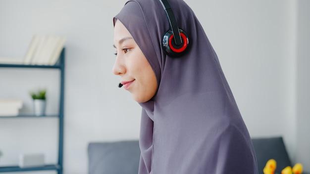 Asiatische muslimische dame trägt kopfhörer-uhr-webinar hören sie den online-kurs per konferenz-videoanruf zu hause.