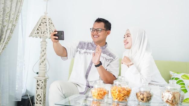 Asiatische muslimische familien feiern eid gemeinsam bei videoanrufen