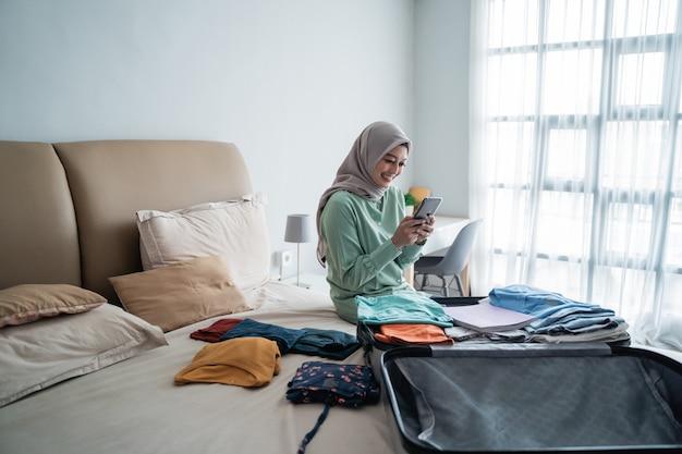 Asiatische muslimische frau, die abflugpläne über handy sucht