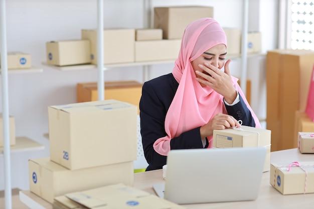 Asiatische muslimische frau, die beim arbeiten am holztisch mit computer- und paketkastenlieferung gähnt.