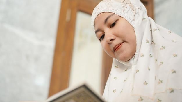 Asiatische muslimische frau, die den koran in der moschee liest