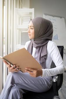 Asiatische muslimische frau, die ein buch im amt liest