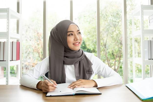 Asiatische muslimische frau, die ein buch in ihrem büro schreibt