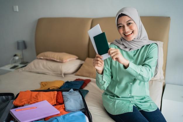 Asiatische muslimische frau, die eine karte hält, nachdem sie ihre kleidung vorbereitet hat