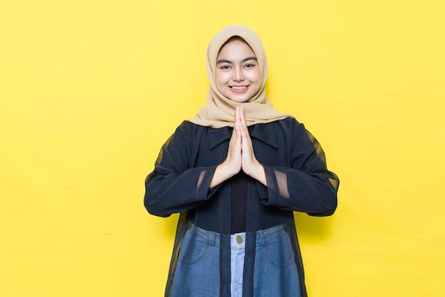 Asiatische muslimische frau, die gäste begrüßt