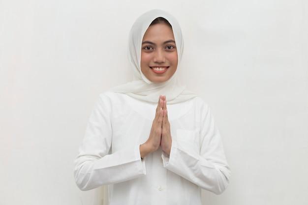 Asiatische muslimische frau, die gastgeste begrüßt