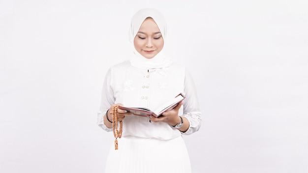 Asiatische muslimische frau, die gebetsperlen trägt, beten im weißen raum